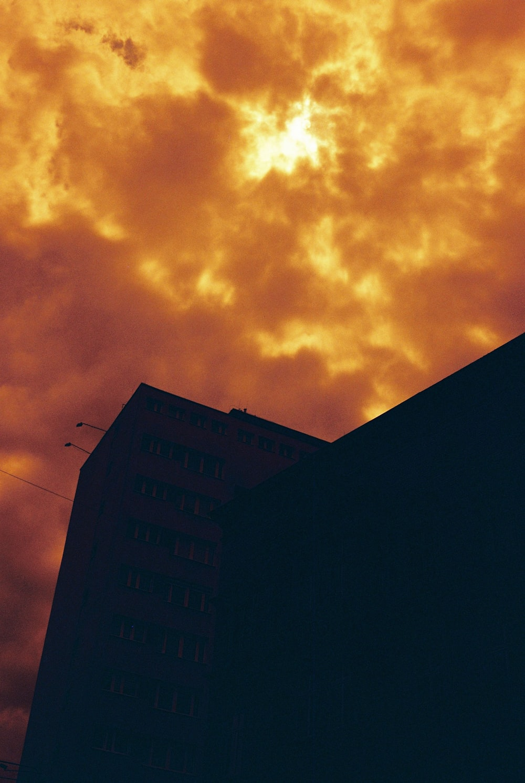 silhouette of building under orange clouds
