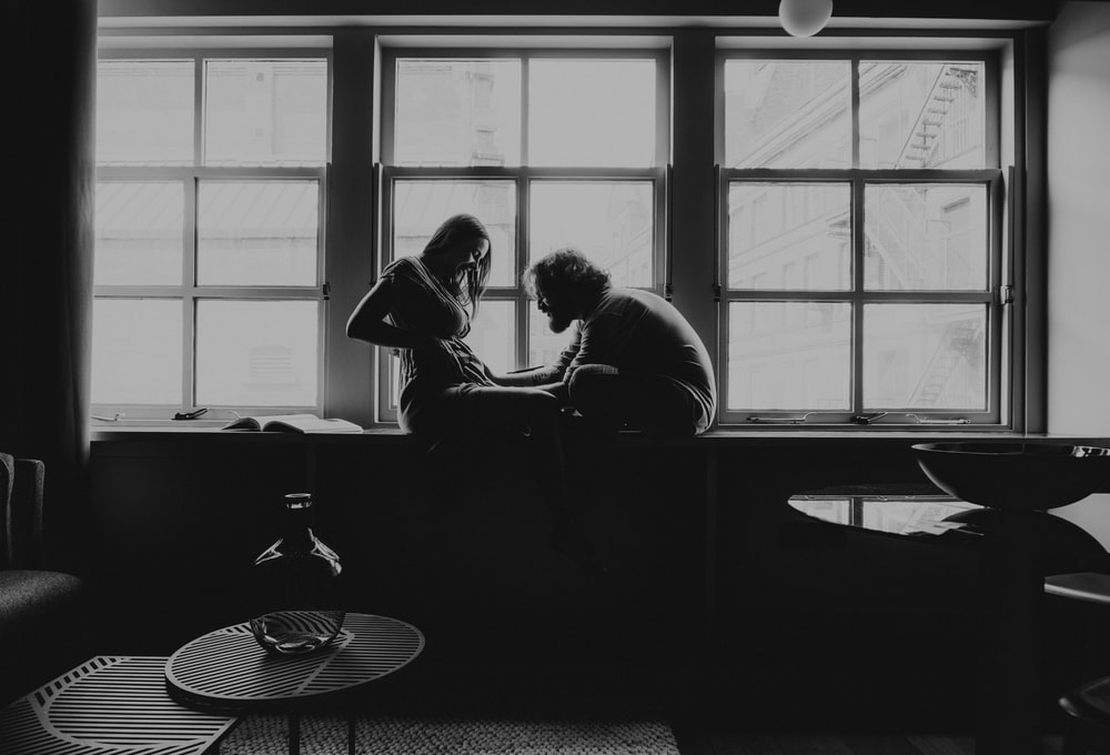 man and woman sitting on chair in grayscale photography