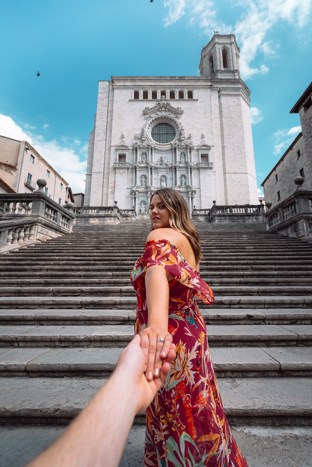 woman in red and white floral dress sitting on stairs