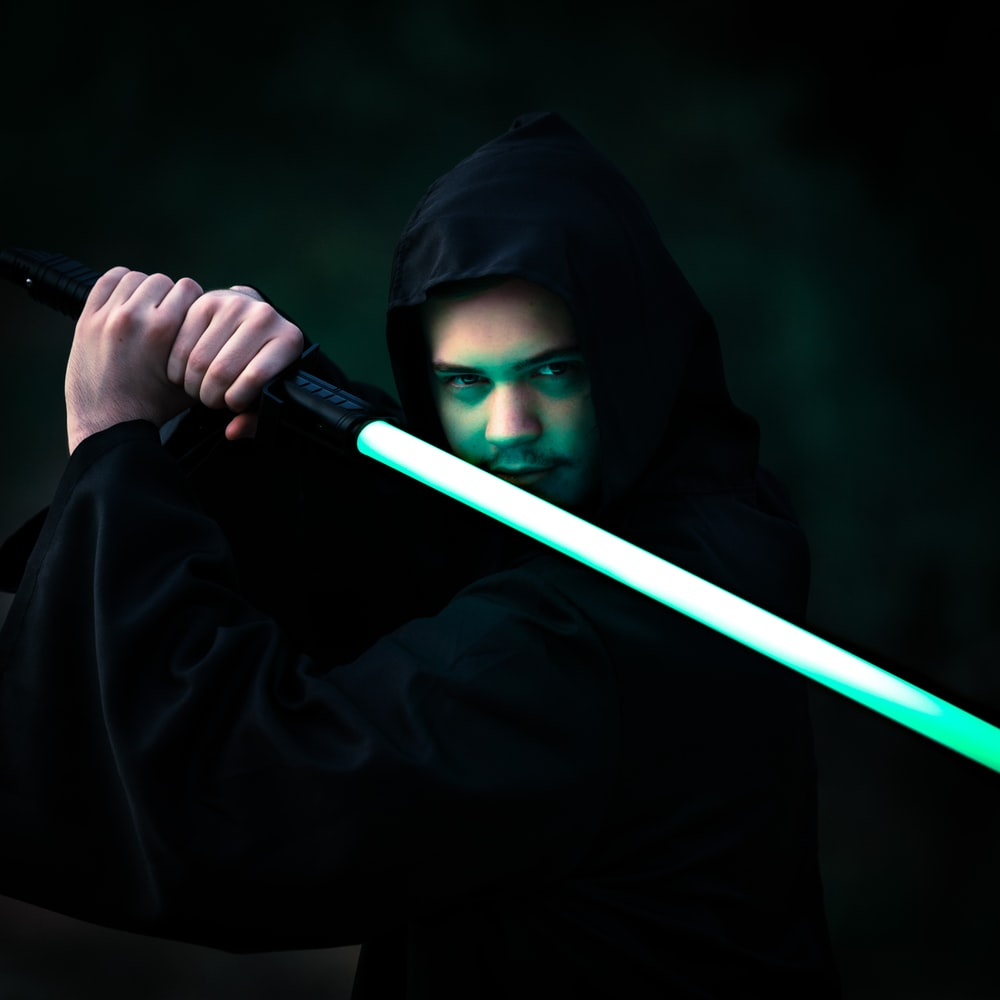 person in black hoodie holding blue stick