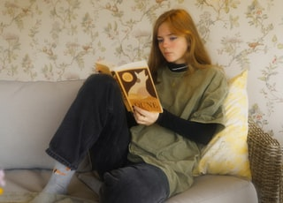 woman in black jacket sitting on white couch