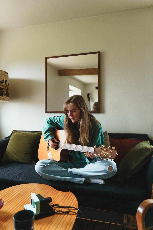 woman in green long sleeve shirt playing white electric guitar
