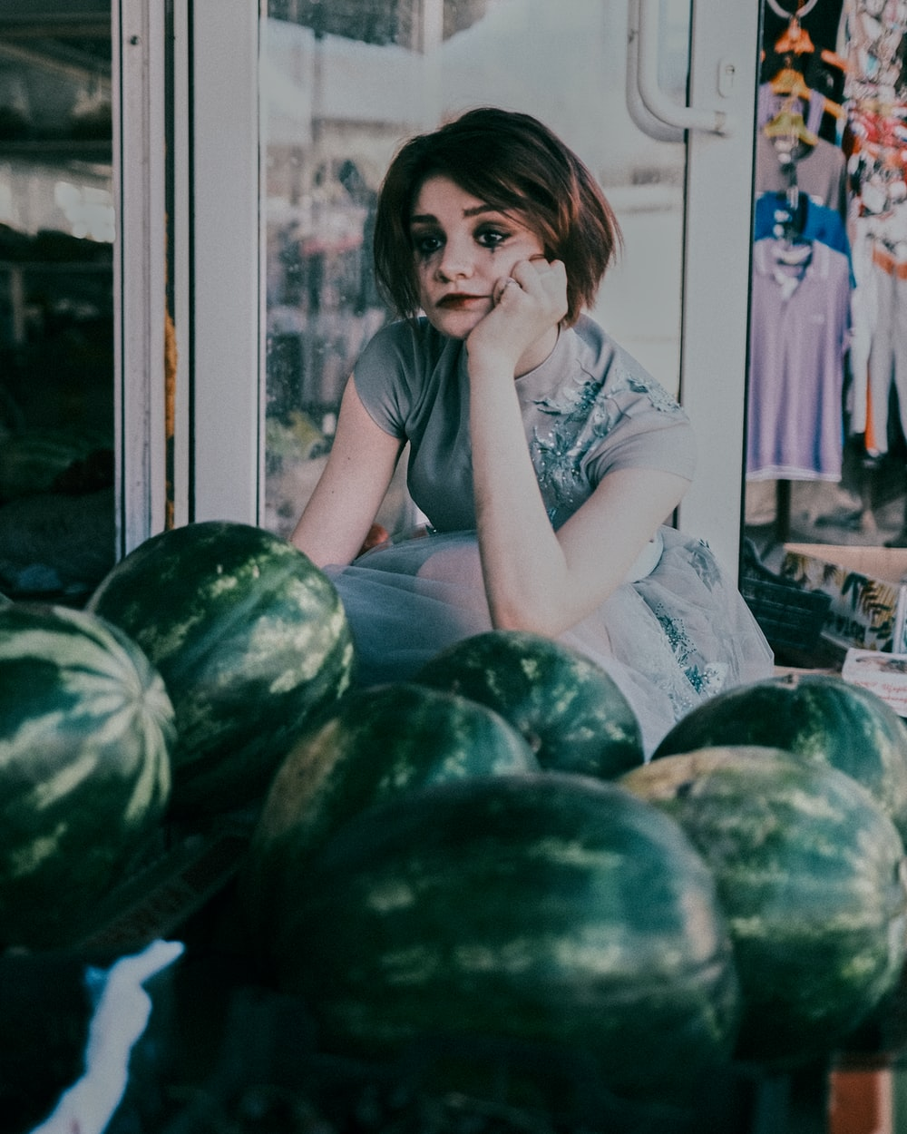 woman in white shirt sitting on green watermelon