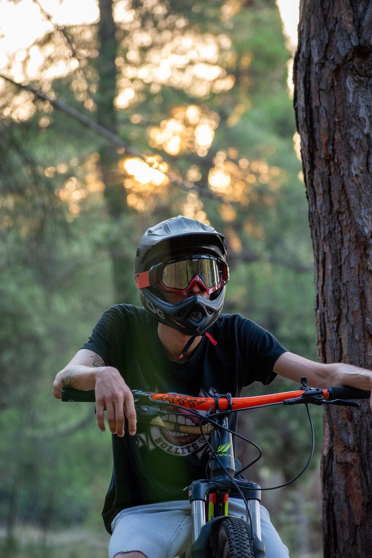 man in black jacket wearing helmet riding bicycle