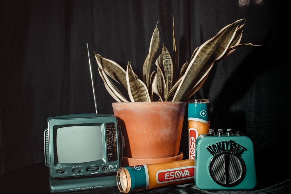 orange plastic cup beside black and gray radio