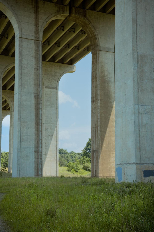 gray concrete bridge over green grass field during daytime