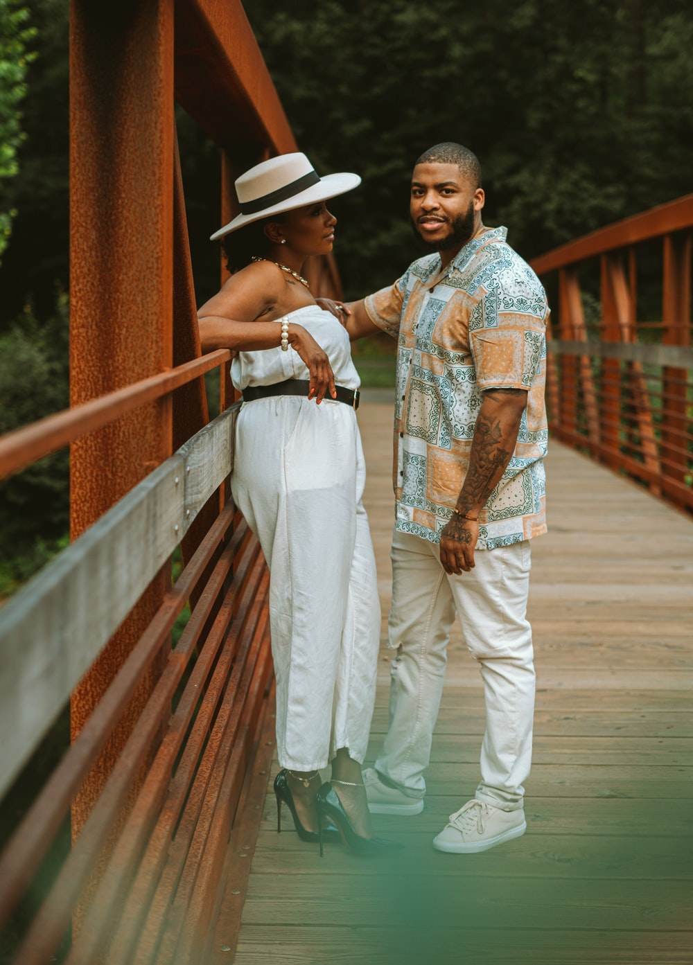 man in white pants and woman in white dress walking on wooden bridge during daytime