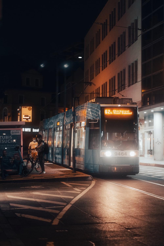 people walking on sidewalk near white and yellow tram during night time