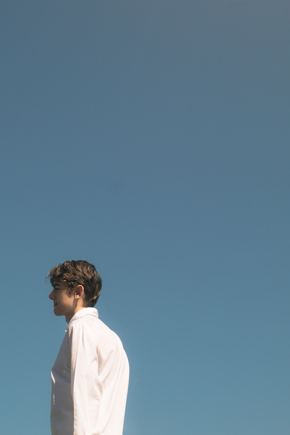 man in white shirt standing under blue sky during daytime