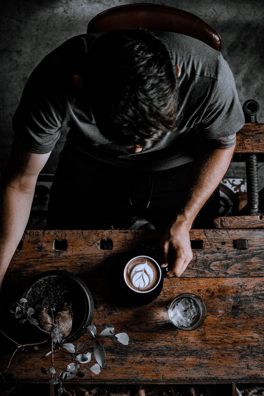 man in black t-shirt holding black ceramic mug