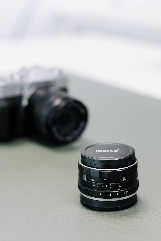 black nikon camera lens on white table