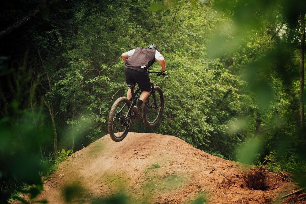man in black jacket riding black mountain bike on brown dirt road between green trees during