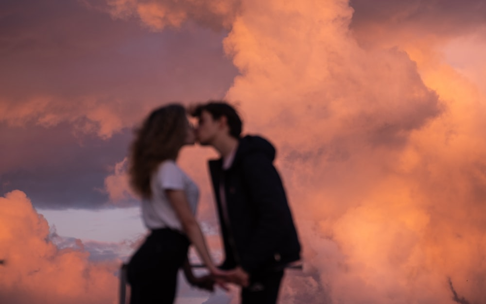 man and woman kissing under cloudy sky during daytime