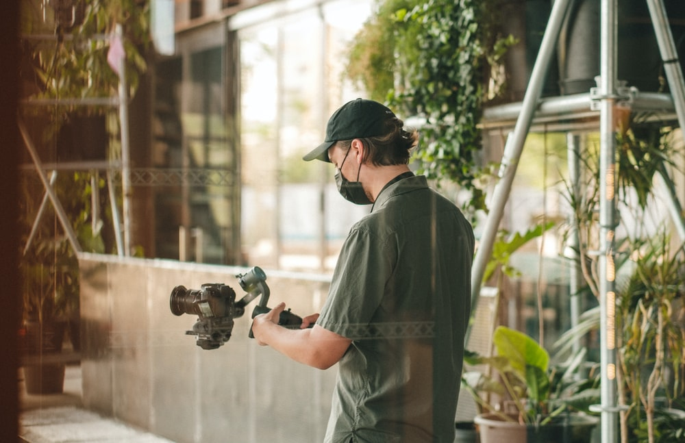 man in gray dress shirt holding black dslr camera