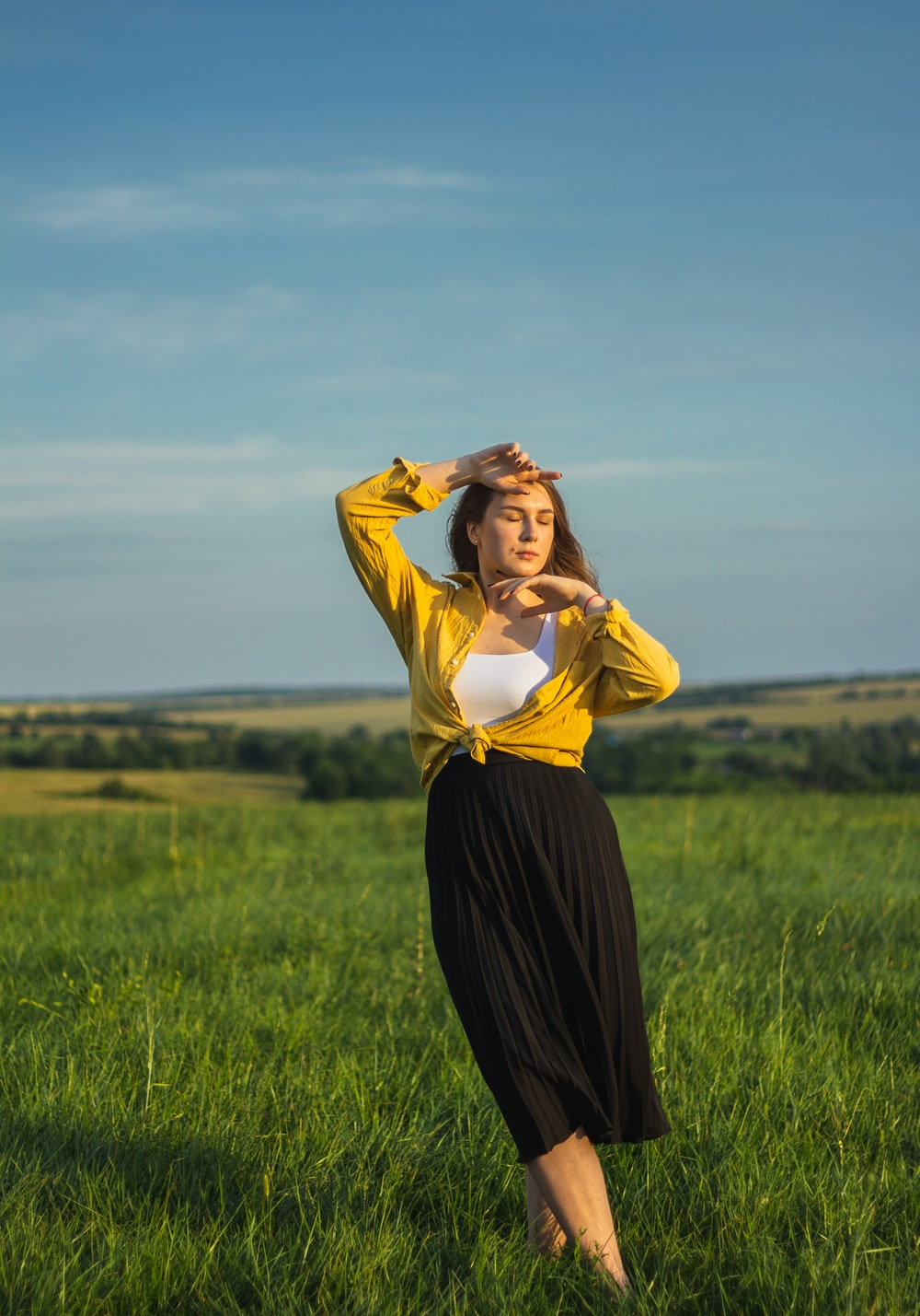 woman in yellow long sleeve shirt and black skirt standing on green grass field under blue