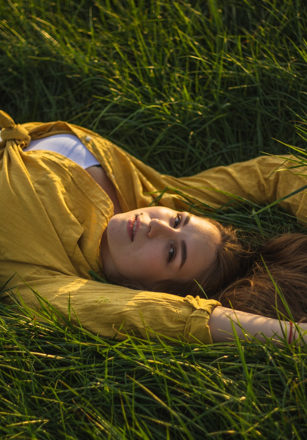 woman in brown coat lying on green grass during daytime