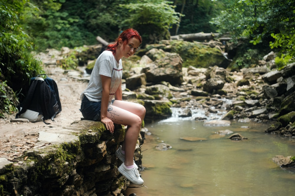 woman in white t-shirt sitting on rock near river during daytime