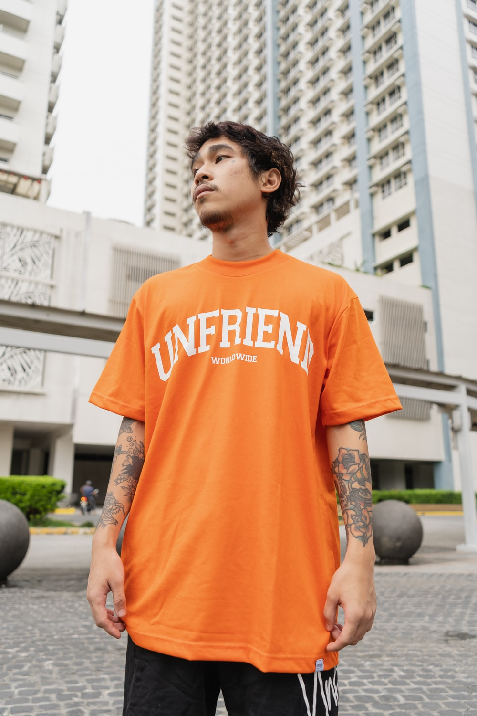 man in orange crew neck t-shirt standing near black round ball during daytime