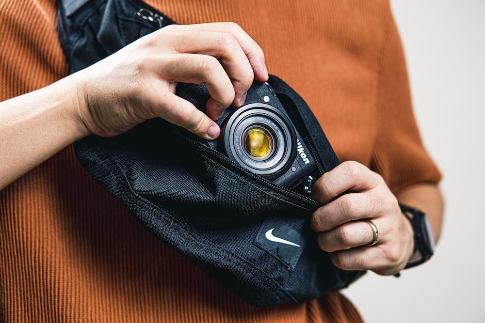 person holding black camera on orange textile