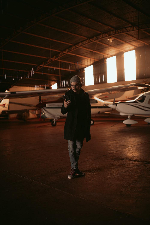 man in black jacket standing near white airplane