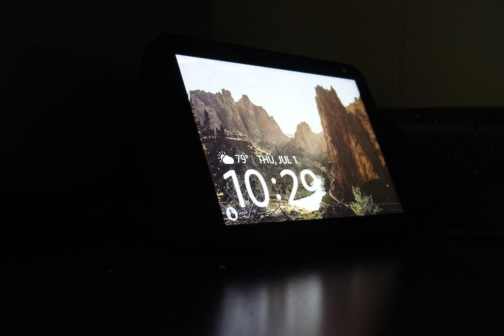 black tablet computer turned on displaying 12 00