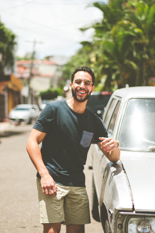 man in black crew neck t-shirt standing beside white car during daytime