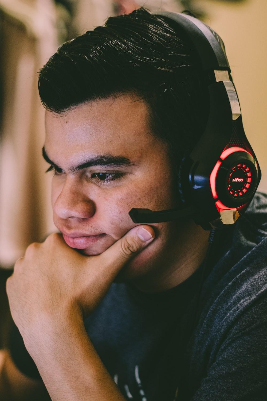 man in black crew neck shirt wearing black and red headphones