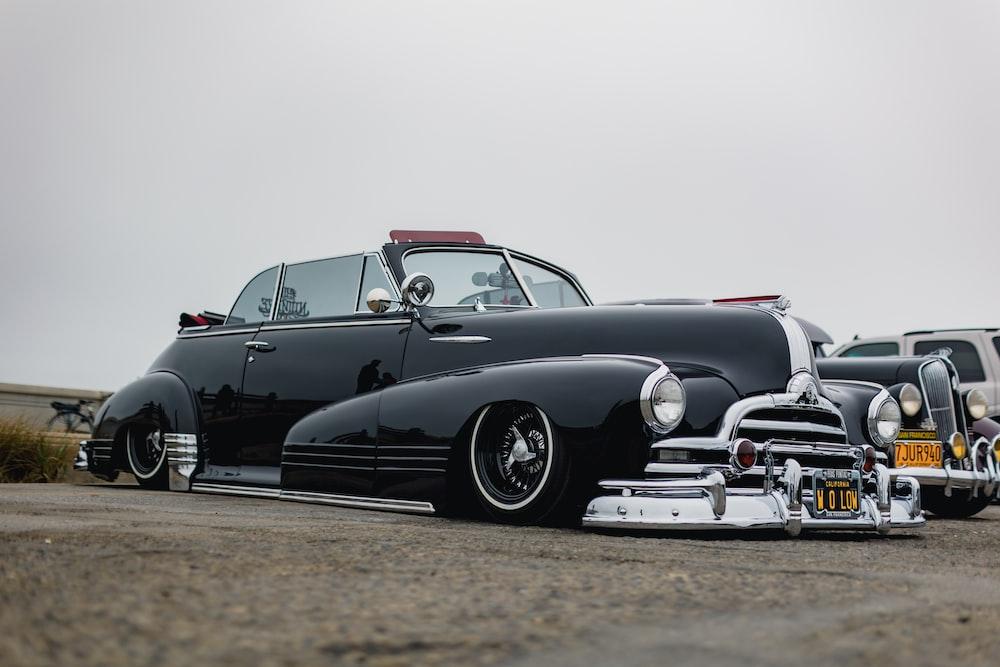 black vintage car on gray asphalt road during daytime
