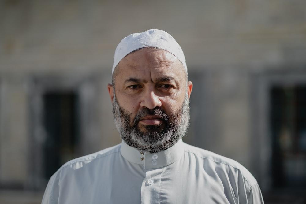 man in white thobe and white taqiyah
