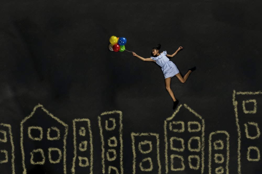 man in white t-shirt and blue shorts playing with green ball