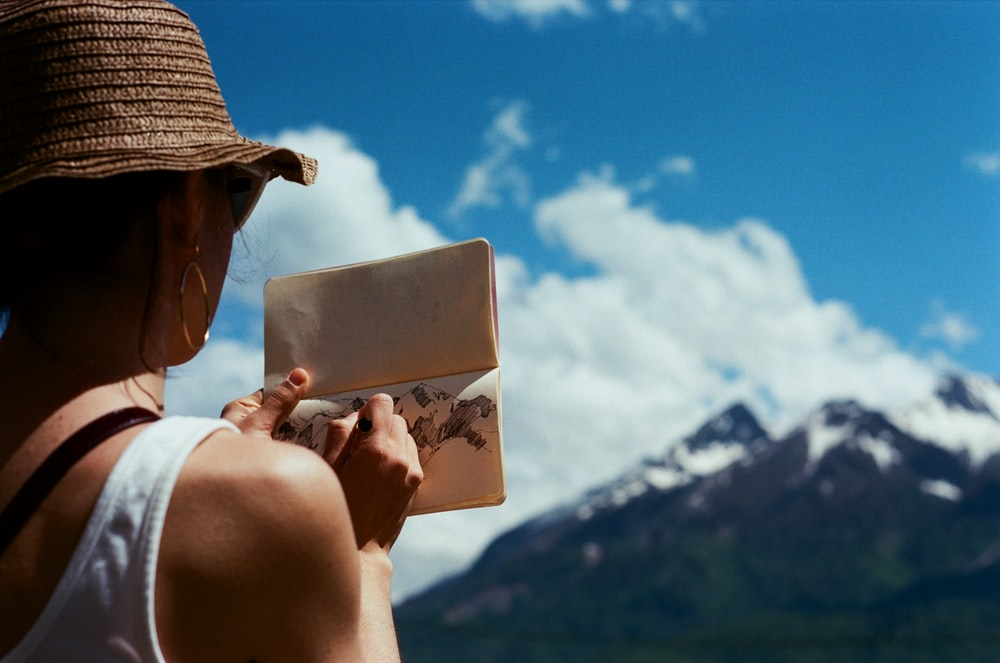 man wearing brown hat holding white card