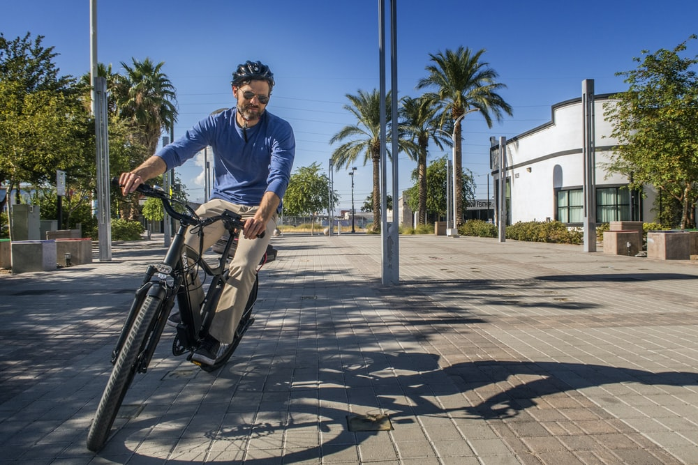 man in blue polo shirt riding bicycle during daytime