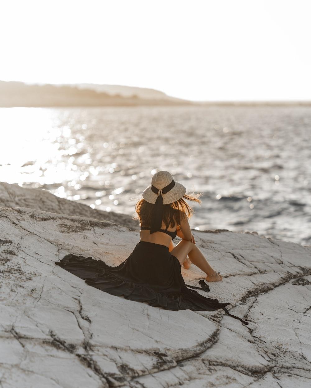 woman in black bikini sitting on rock formation during daytime