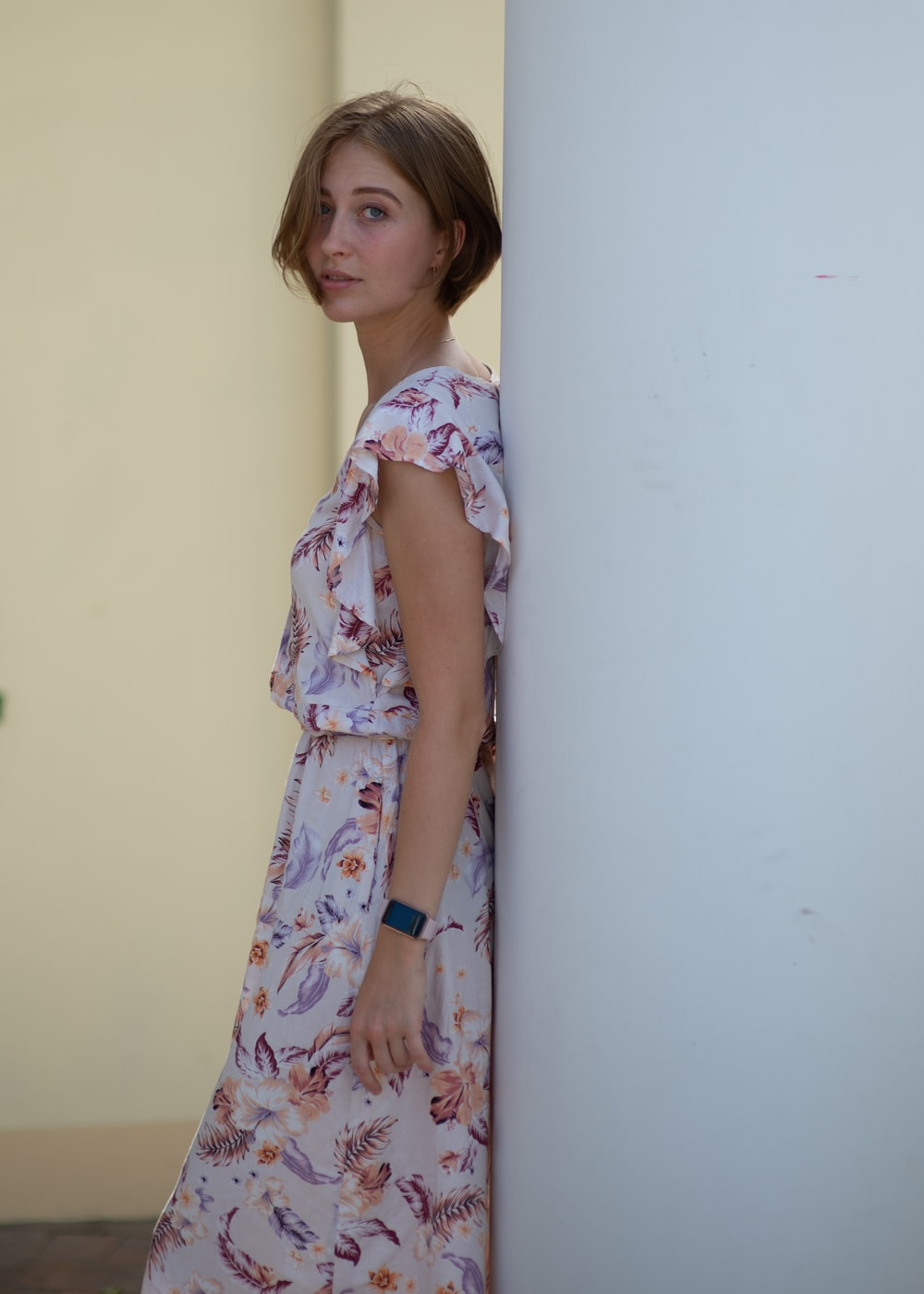 girl in white pink and blue floral dress standing beside white wall