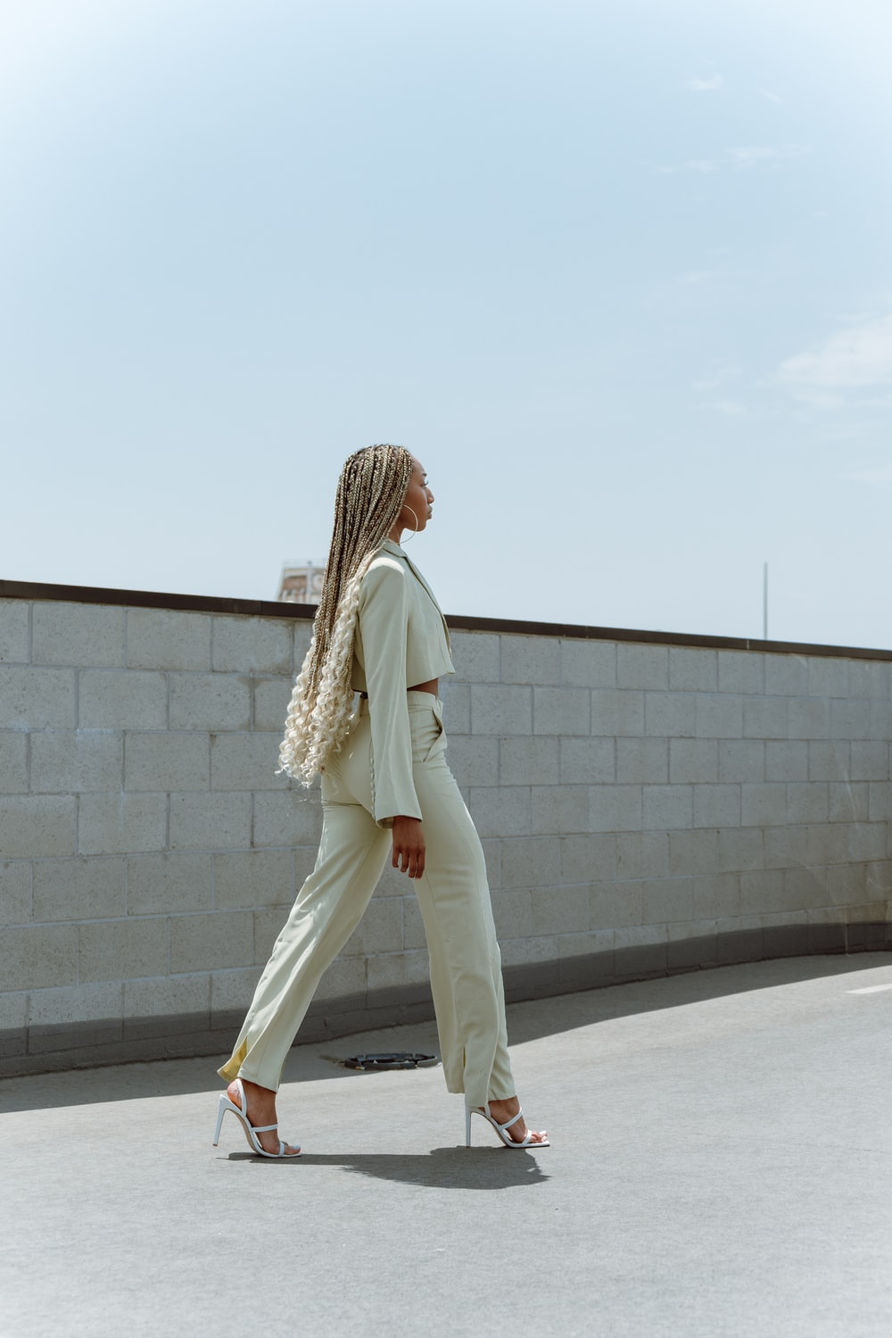 woman in white pants and white cardigan standing on gray concrete floor during daytime