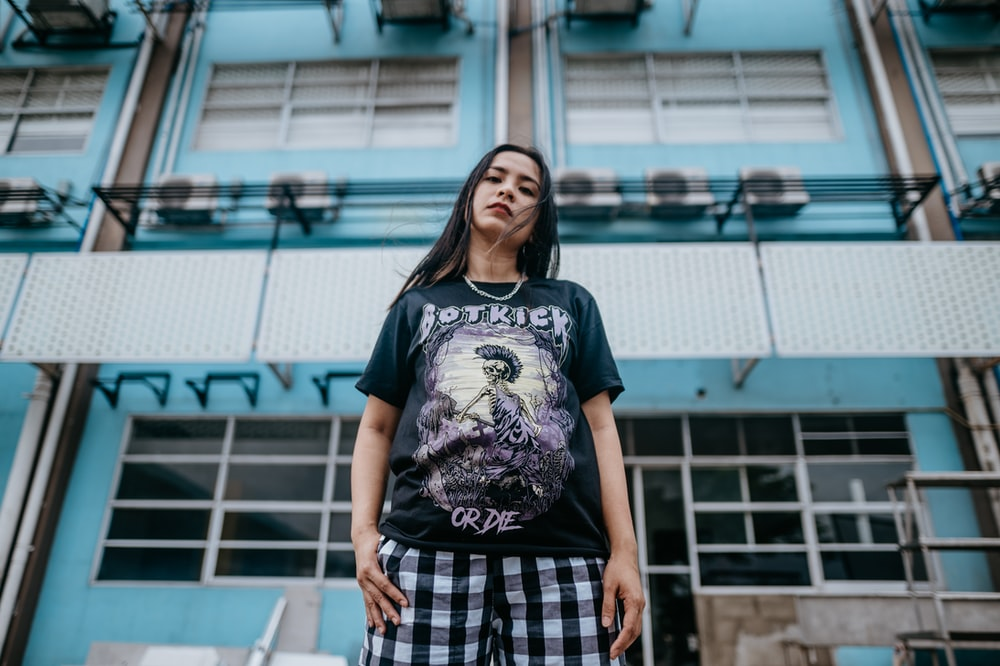 woman in black crew neck t-shirt and black and white plaid skirt standing on gray