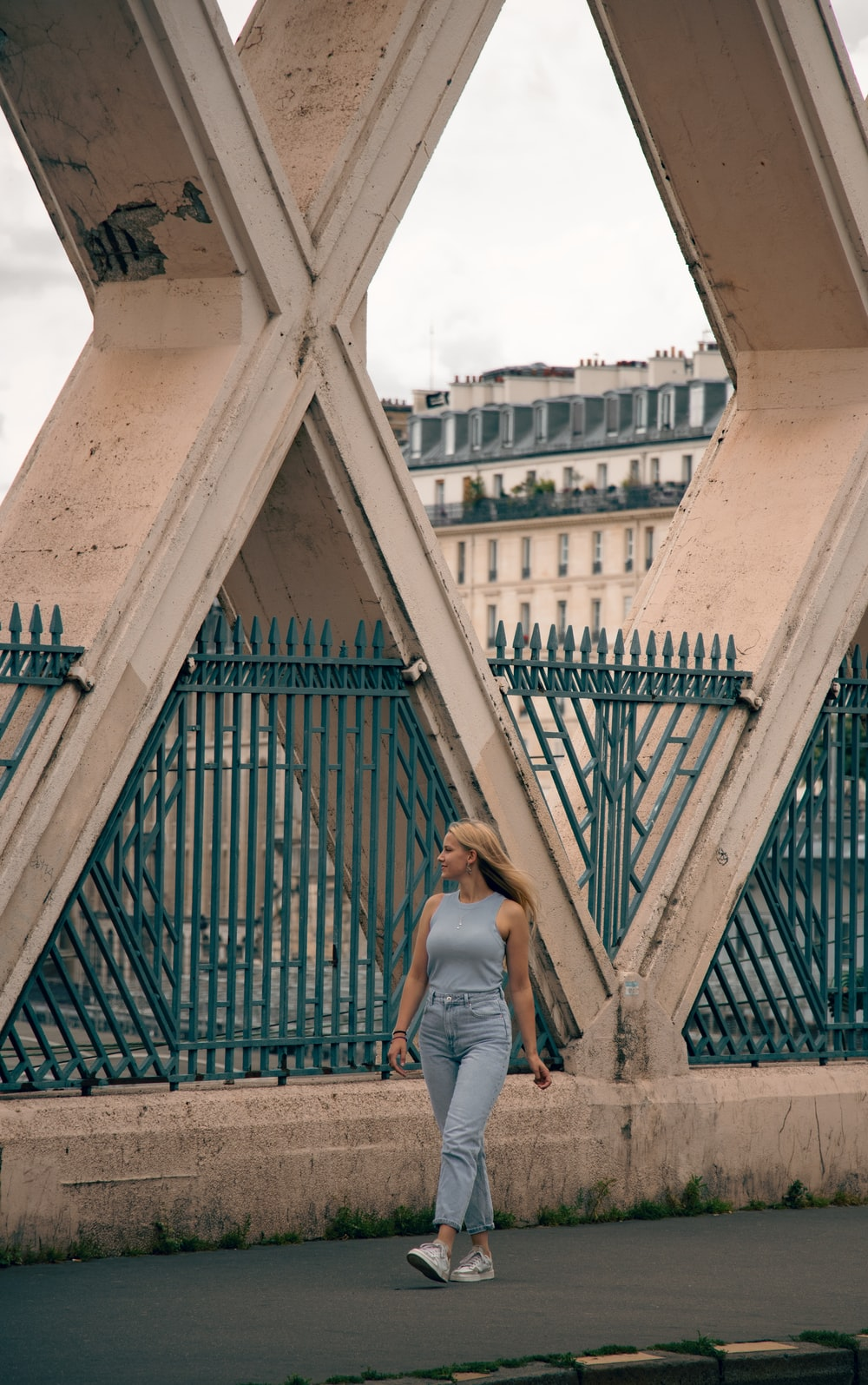 woman in white tank top and blue denim jeans standing on brown concrete bridge during daytime