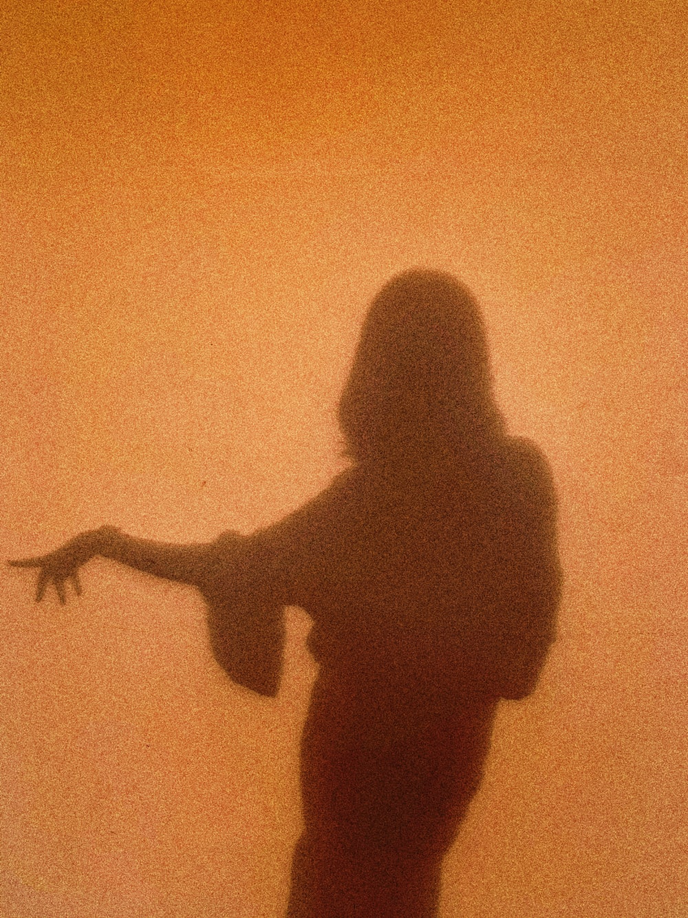 silhouette of woman standing and raising her right hand