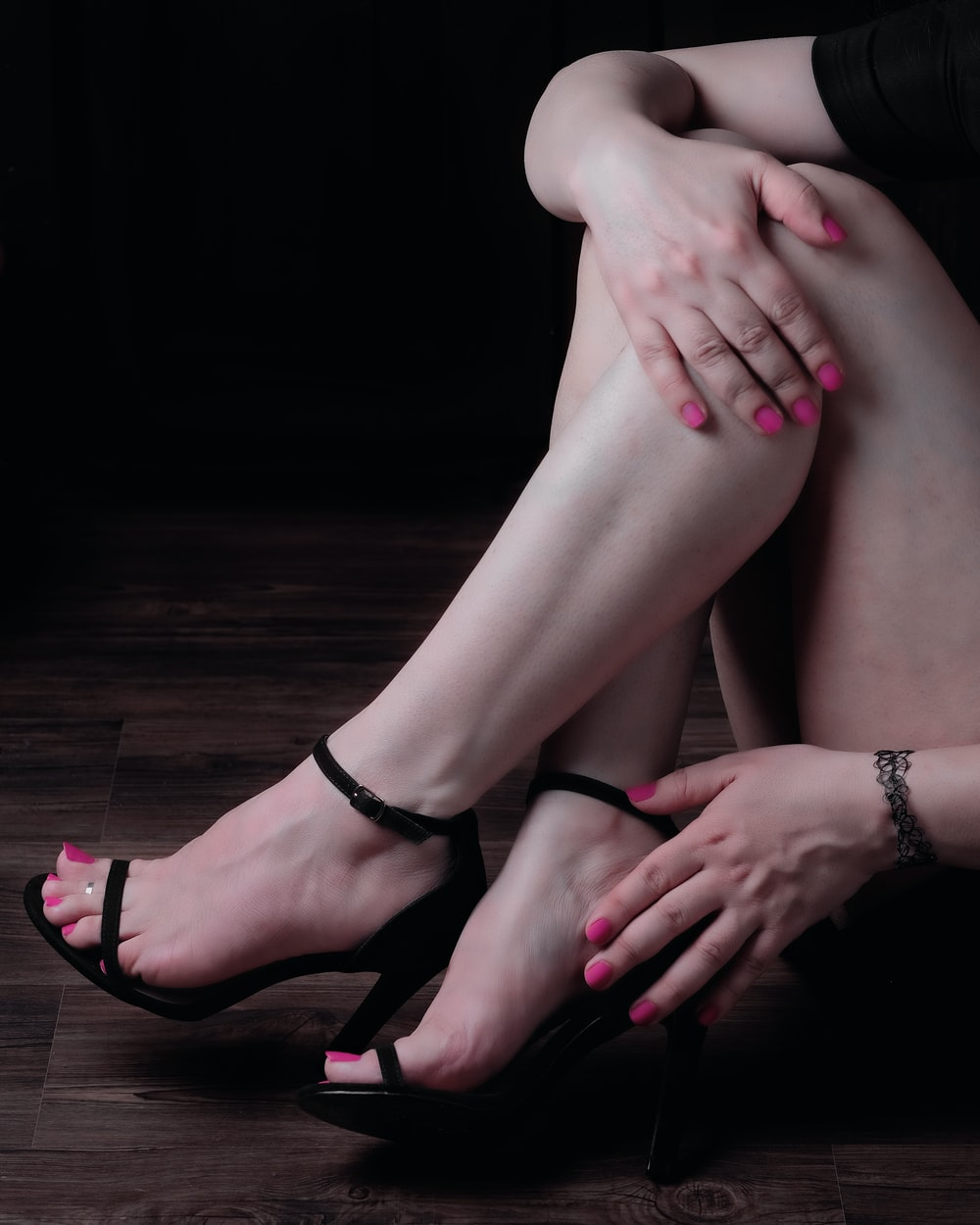 person wearing black leather peep toe heeled sandals