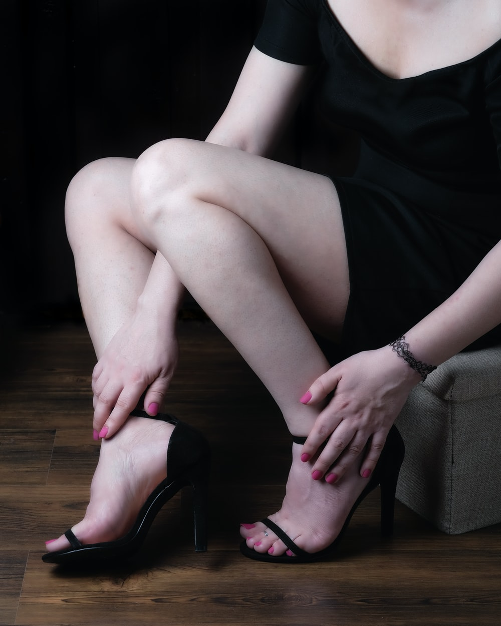 woman in black dress sitting on gray sofa