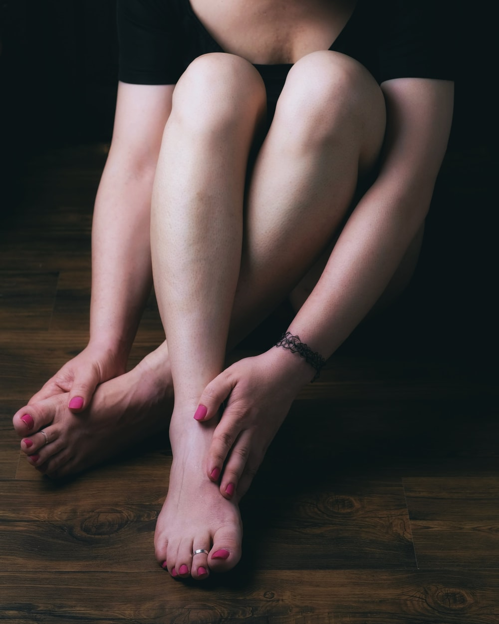 woman in black shorts sitting on brown wooden floor