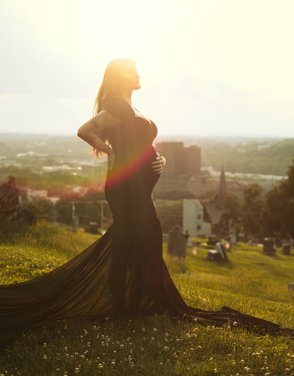 woman in black dress standing on green grass field during daytime
