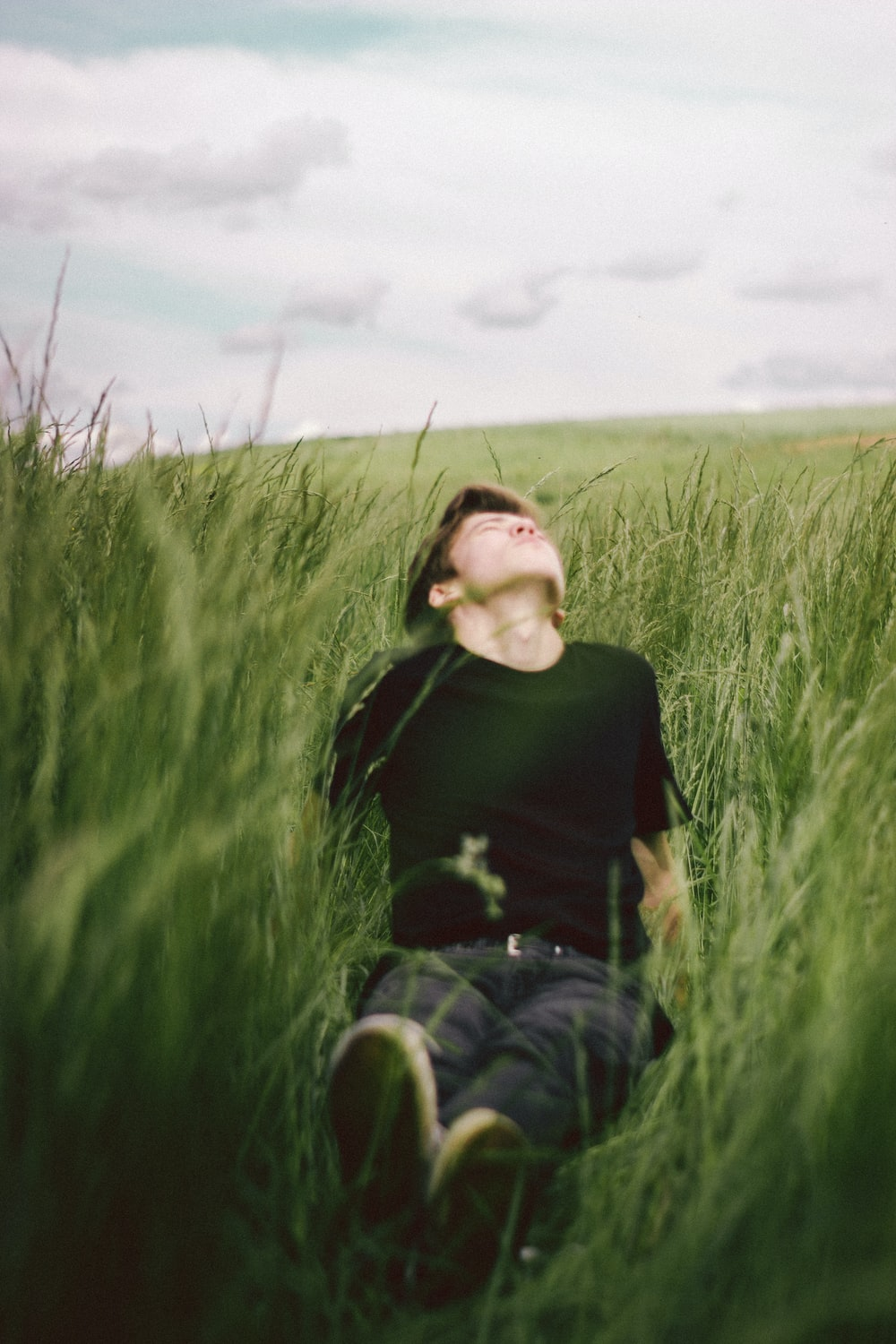 woman in black long sleeve shirt and blue denim jeans sitting on green grass field during