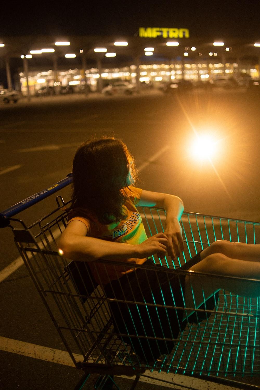girl in green tank top sitting on shopping cart