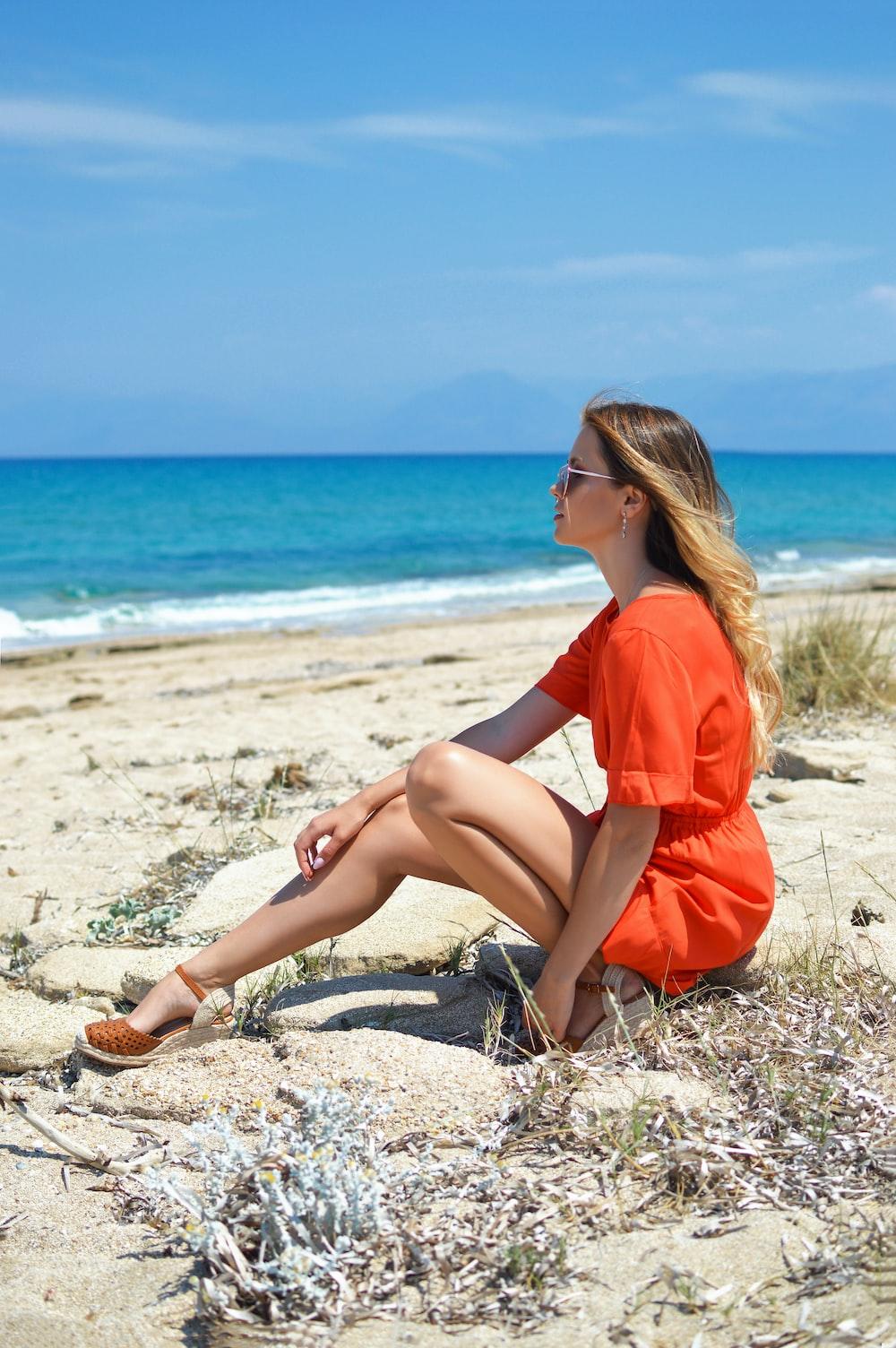 woman in orange dress sitting on beach shore during daytime
