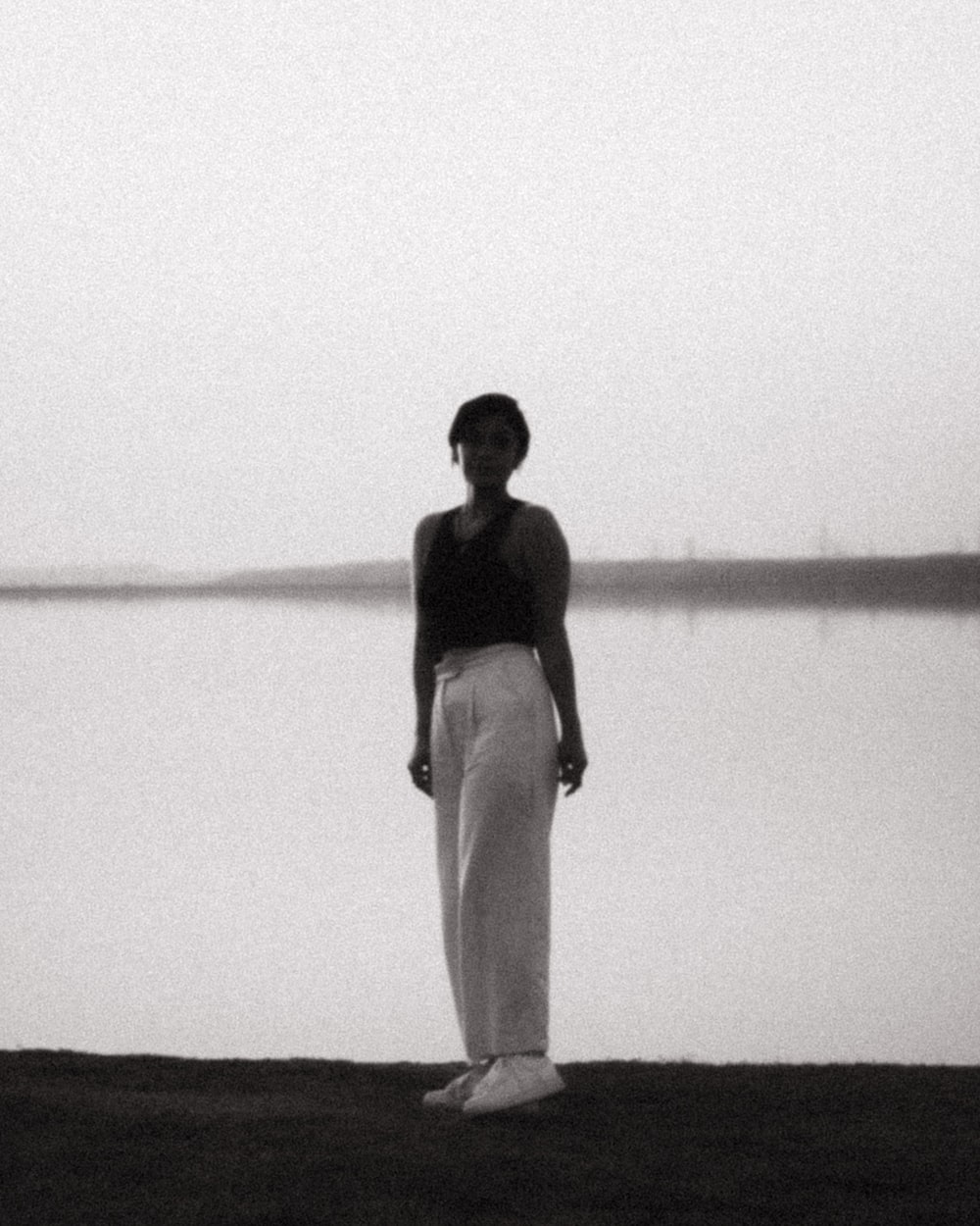 woman in black tank top and white pants standing on shore