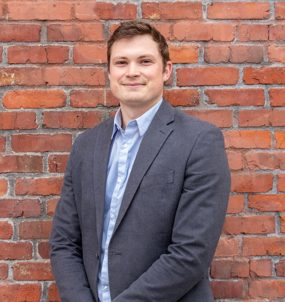 man in gray suit jacket standing beside brown brick wall