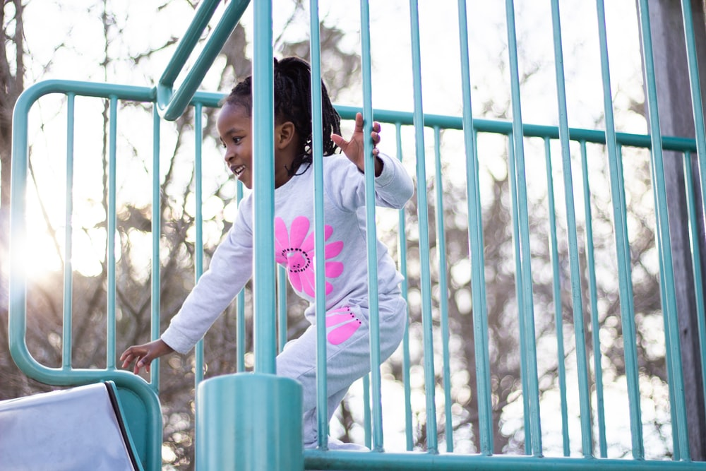 girl in pink hoodie and blue pants standing beside blue metal fence during daytime