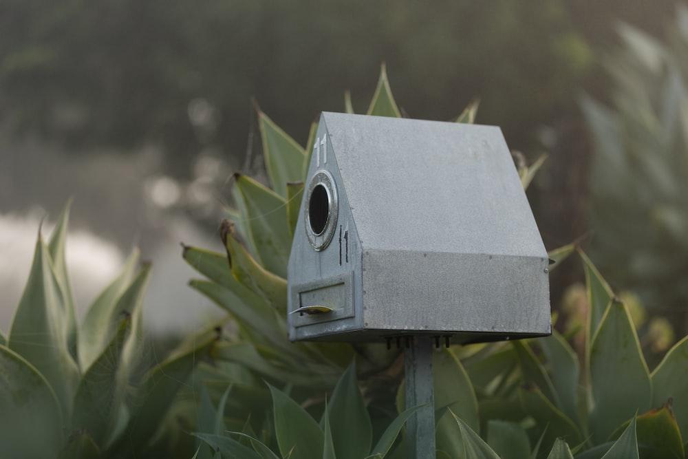 brown wooden bird house on green grass
