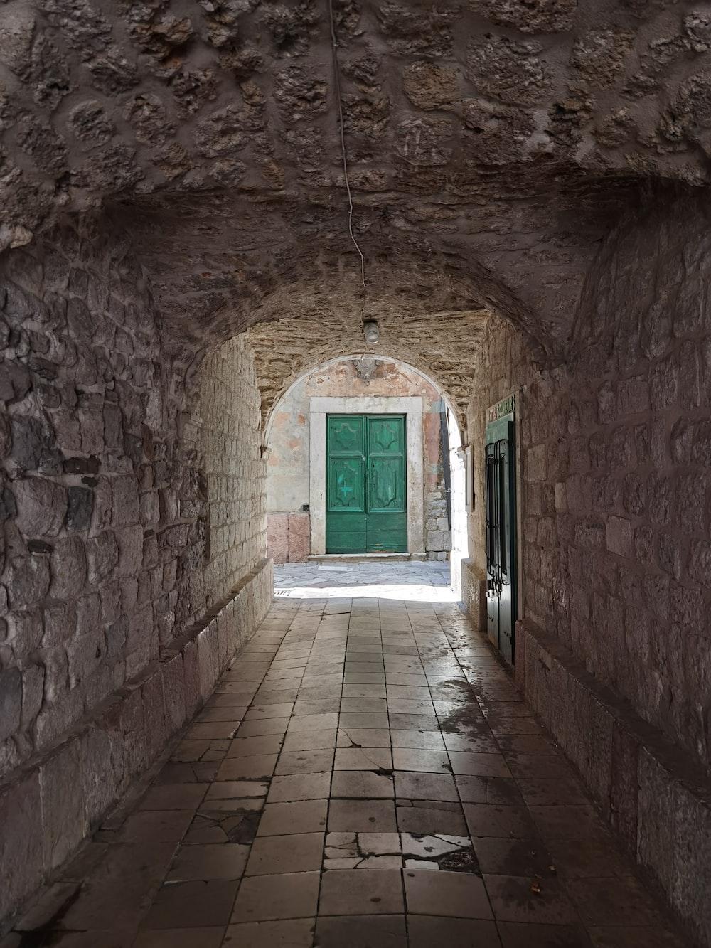 brown brick hallway with blue wooden door
